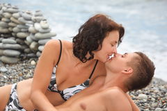 Woman is kissing her man on sea coast Royalty Free Stock Photography