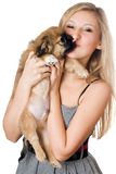 Woman kissing her puppy Stock Photos