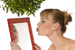 Woman kissing herself in a mirror under mistletoe. Naked woman kissing herself in a mirror under mistletoe isolated on white Royalty Free Stock Photo