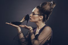 Woman kissing high heel shoe Stock Images
