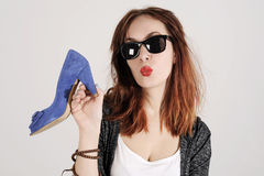 Woman kissing and holding a shoe. Women loves shoes concept. Fashion girl and blue high heels shoes. Beautiful young girl Royalty Free Stock Photos