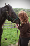 Woman kissing horse. Middle aged red headed woman kissing nose of black horse in countryside stock image