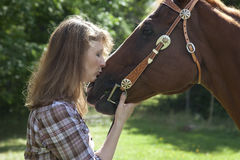 Woman kissing horse. Side view of woman kissing muzzle of brown horse Royalty Free Stock Images