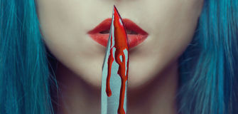 Woman kissing a knife in blood. Young woman kissing a knife in blood. Halloween or horror theme. Close-up image of red lips stock image