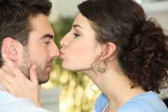 Woman kissing man Stock Photos