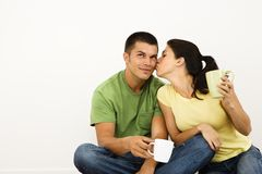 Woman kissing man. Couple sitting on floor drinking coffee with woman leaning over kissing man on cheek stock photo