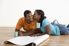 Woman kissing man. African American female kissing man next to blueprints royalty free stock photo
