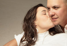 Woman kissing a man. Young woman kissing a young man on his cheek stock photos