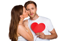 Woman kissing man as he holds heart Royalty Free Stock Images