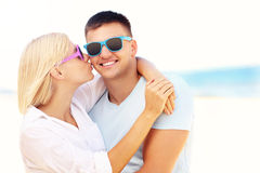 Woman kissing a man at the beach Stock Images