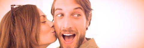 Woman kissing man with beard on cheek. Pretty women kissing men with beard on cheek against white background royalty free stock photo
