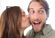 Woman kissing man with beard on the cheek. Pretty women kissing men with beard on the cheek royalty free stock photo