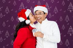 Woman kissing man on cheeks against digitally generated background Royalty Free Stock Photo