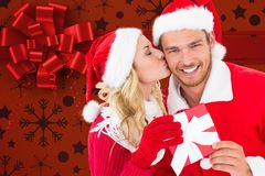 Woman kissing man on cheeks against digitally generated background. Woman kissing men on cheeks against digitally generated background during christmas time stock photography