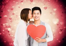 Woman kissing on man cheeks while holding red heart. Against digitally generated heart background royalty free stock photography