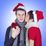 Woman kissing man with Christmas gift box. Happy couple wearing Santa's hats and scarves celebrating Christmas.  Woman wearing Santa's hat kissing men with Stock Image