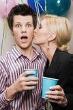 Woman kissing man at Christmas party Royalty Free Stock Images