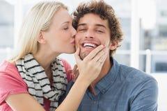 Woman kissing man on his cheek Stock Photos
