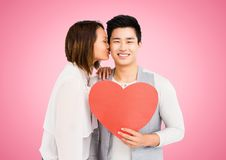 Woman kissing man while holding heart. Against pink background royalty free stock image