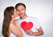 Woman kissing man while holding heart. Against white background stock photos