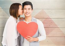 Woman kissing man holding heart. Against wooden background stock photo