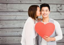 Woman kissing man holding heart Stock Photos