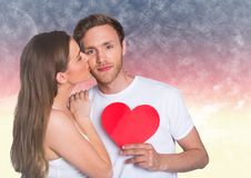 Woman kissing while man holding a red heart. Composite image of woman kissing while man holding a red heart stock images