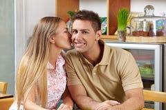Woman Kissing Man On Cheek In Café Stock Photo