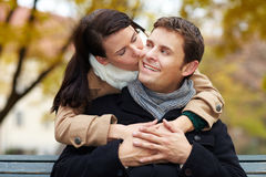 Woman kissing man in park Royalty Free Stock Images