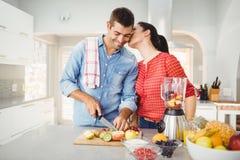 Woman kissing man preparing fruit juice Royalty Free Stock Image