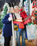 Woman Kissing Man With Stacked Christmas Presents Royalty Free Stock Image