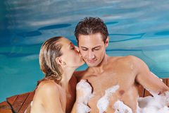 Woman kissing man in whirlpool Stock Images