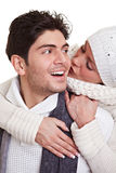 Woman kissing man in winter. Young woman kissing happy man in winter clothes stock image