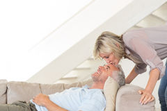 Woman kissing a mans forehead in the living room Stock Images
