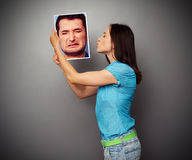 Woman kissing the photo of depressed man Royalty Free Stock Photography