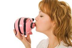 Woman kissing pigg-bank Royalty Free Stock Images