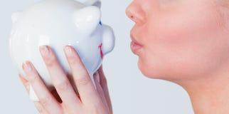 Woman kissing a piggy Bank Royalty Free Stock Photo