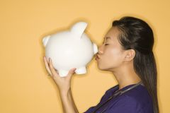 Woman kissing piggy bank. Royalty Free Stock Photo