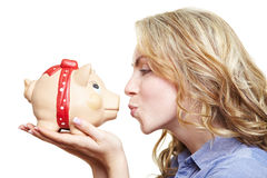 Woman kissing piggy bank Royalty Free Stock Images