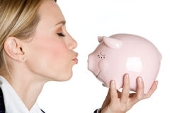 Woman Kissing Piggy Bank. Beautiful woman kissing piggy bank Royalty Free Stock Photography
