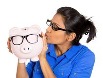 Woman kissing piggy bank with glasses Stock Photo
