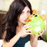 Woman kissing piggy bank happy Stock Photo