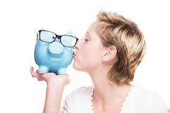 Woman kissing a piggy bank Stock Image