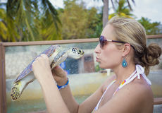 Woman kissing a sea turtle Stock Photography