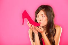 Woman kissing shoe. Women loves shoes concept. Multiracial girl and pink high heels shoes on pink background. Beautiful young happy mixed race Asian Chinese Stock Photos