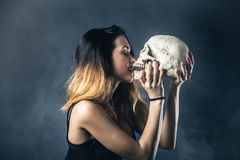 Woman kissing skull Stock Image