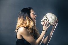 Woman kissing skull Royalty Free Stock Photography