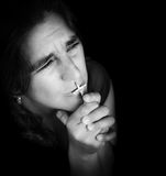Woman kissing a small crucifix and looking up Stock Photo