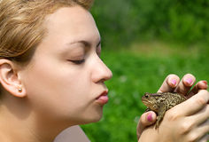 Woman kissing a toad Royalty Free Stock Images