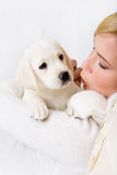 Woman kissing white puppy of Labrador Stock Images